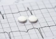 Two aspirin tablets on a patient electrocardiograph.